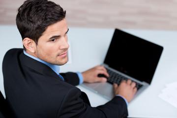 junger geschäftsmann schreibt am laptop