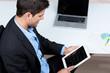 geschäftsmann mit tablet und notebook am arbeitsplatz
