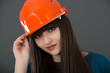 Businesswoman with construction helmet. Isolated on gray