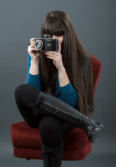 Young woman with retro camera over dark background