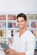 lächelnder mann mit tablet in der bibliothek