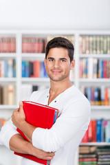 student mit ordner in der bibliothek