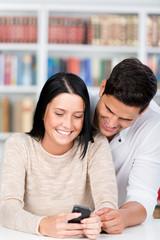 junges paar mit handy in der bibliothek