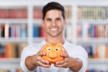 lächelnder student zeigt sparschwein