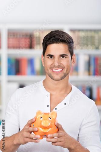 lächelnder student mit sparschwein