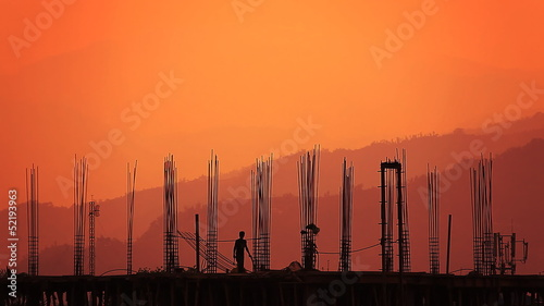 Silhouette of  worker and building against a sunrise.