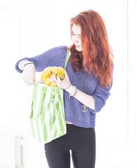 Happy woman put fruit in eco friendly cloth bag