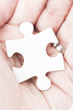 Palm of human hand hold white piece of a puzzle