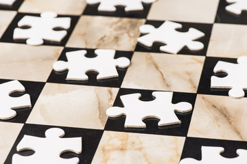 Blank puzzle pieces on chess board