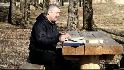 Man reading a book outdoors on a bench in the park