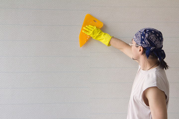 Man smoothing wallpaper with spatula