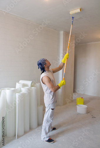worker painting ceiling with painting roller