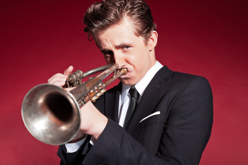 Retro fifties trumpet player wearing black suit. Playing trumpet