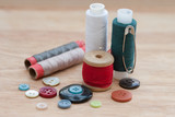 colorful spools of thread, buttons on the wooden background