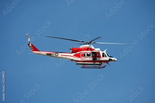 Tuinposter Helicopter patrol helicopter of firefighters in blue sky over a fire 9