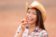 American cowgirl eating peach smiling happy