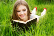 Young woman lies on green grass and reads book