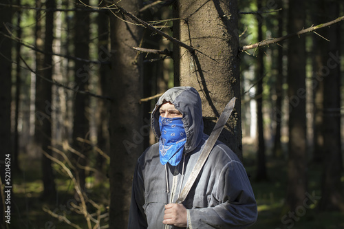 Man with a machete in the woods leaning against tree