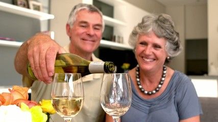 Smiling man pouring glass of white wine for his wife