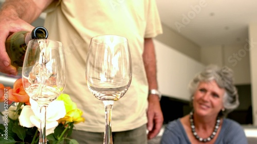 Man pouring glass of wine for his wife