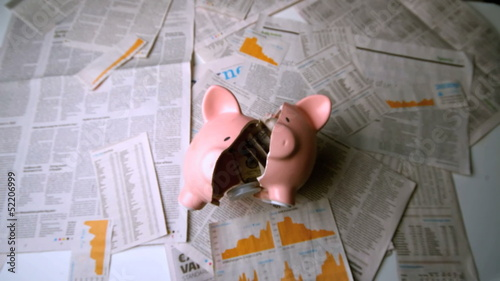Piggy bank falling and being broken over sheets of paper