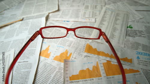 Glasses falling over sheets of paper showing yellow charts