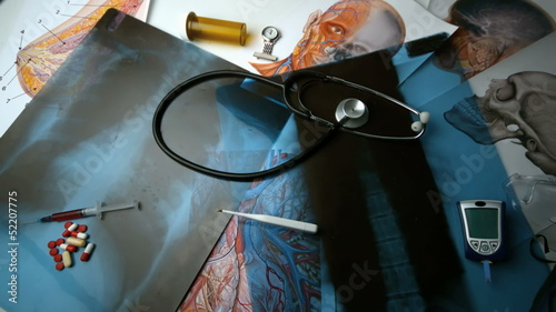 Thermometer falling over x ray beside medical tools