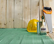 green wood floor with a brush, saw and helmet