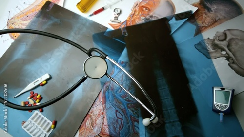 Stethoscope falling over x ray beside other medical tools