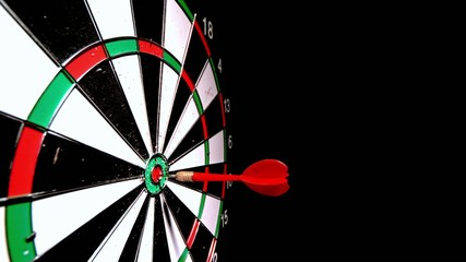Red dart hitting the bulls eye on black background