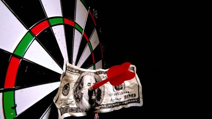 Red dart with a dollar note hitting dart board