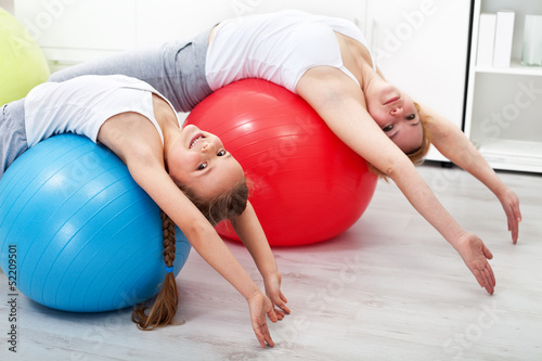 Woman and little girl doing stretching exercises