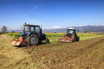 tractors plowing a field