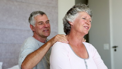 Woman enjoying shoulder massage given by her husband