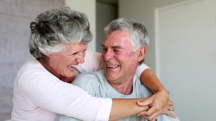 Mature couple laughing and embracing together