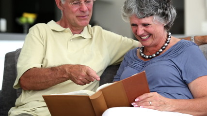 Mature couple laughing while looking at a book