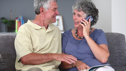 Mature couple having a phone conversation while reading a book