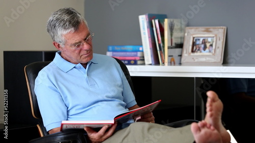 Barefoot man relaxing on a chair while reading a book