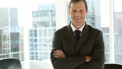 Smiling businessman standing by window