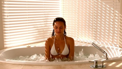 Attractive brunette relaxing in the jacuzzi