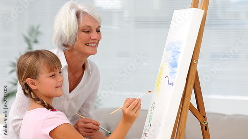 Granny and granddaughter painting a picture