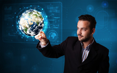 Young businessman touching high-tech 3d earth panel