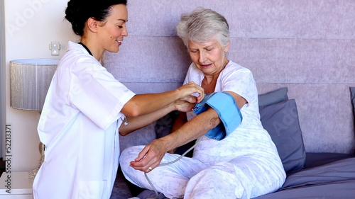 Home nurse checking patients blood pressure