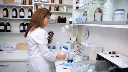 Female pharmacist putting in order medicine in lab