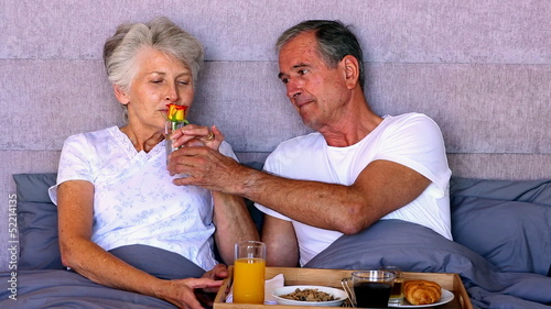 Elderly couple having breakfast in bed