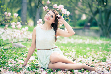 Beautiful young woman sitting under a magnolia tree in bloom