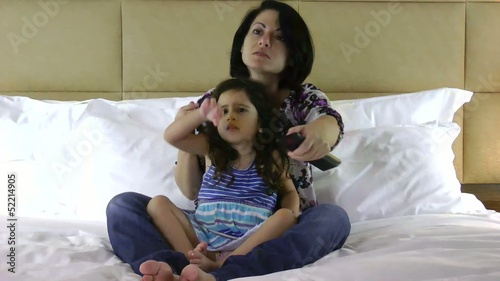 Mother and daughter watching scary movie on the bed
