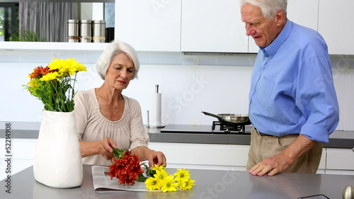 Woman arranging flowers and holds one to husbands nose