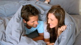 Couple having fun wrapped in their duvet