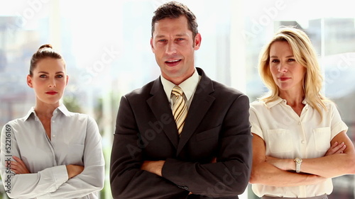 Three smiling business people standing